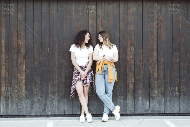 Beautiful women looking at each other while leaning against brown wooden wall