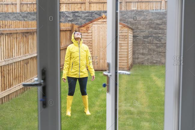 Mid adult woman enjoying rain while standing in back yard during rainy season