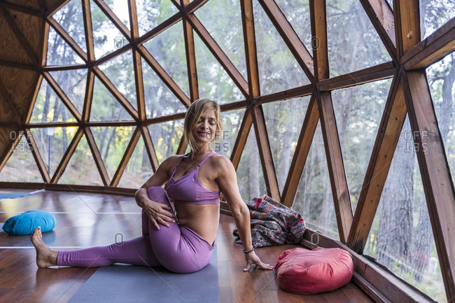 Smiling flexible blond woman practicing yoga against window at health retreat