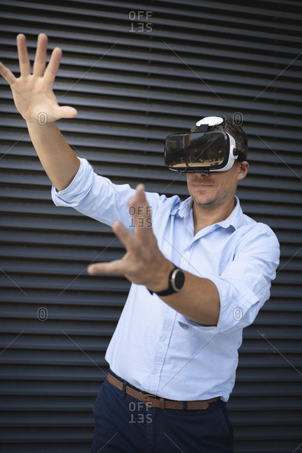 Businessman wearing virtual reality goggles while standing against metal wall