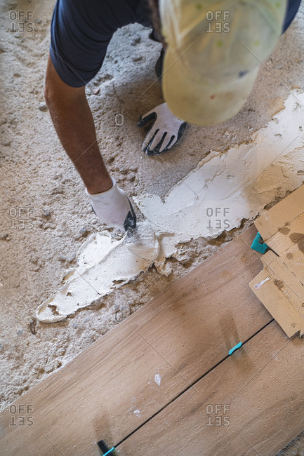 High angle view of male manual worker laying cement on parquet floor in house