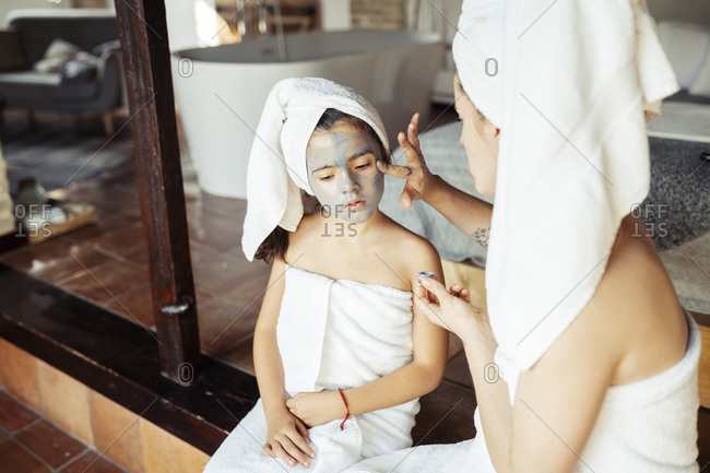 Mother in towel applying facial cream on daughter face while sitting at home