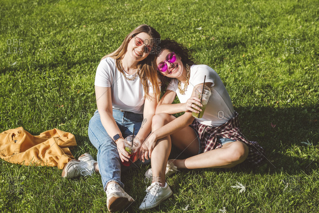 Happy female friends sitting with lemonade on grass at park during sunny day