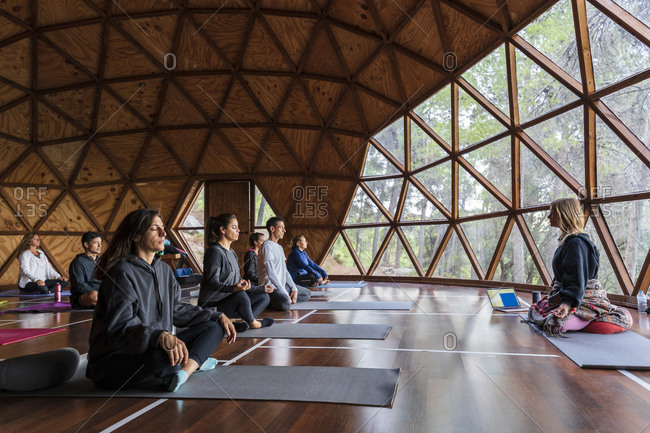 Yoga instructor and tourists practicing breathing exercise at health retreat