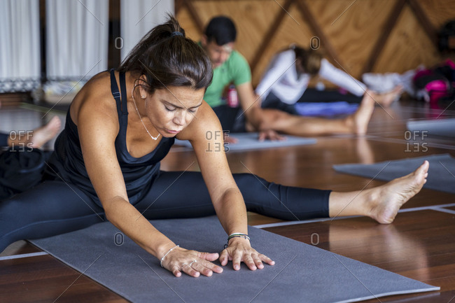 Woman practicing yoga with legs apart on mat in exercise class at health spa
