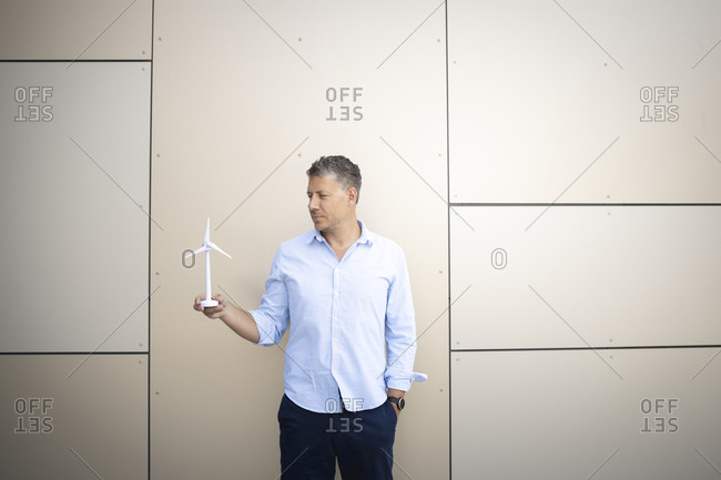 Businessman with hands in pockets holding wind turbine standing against wall