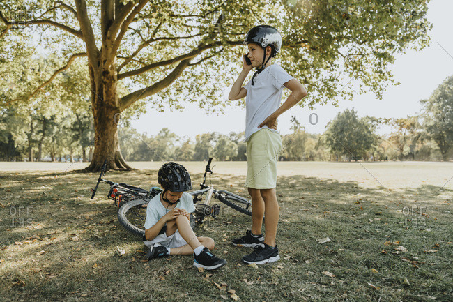 Boy talking on smart phone while brother holding hurt sitting in public park