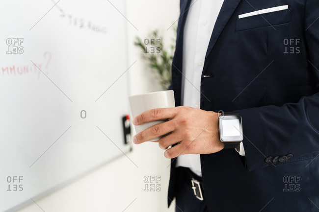Male professional holding coffee cup while standing by whiteboard in office