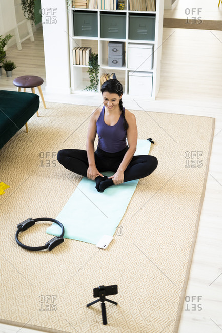 Young woman video recording on camera while sitting in cobbler pose at home