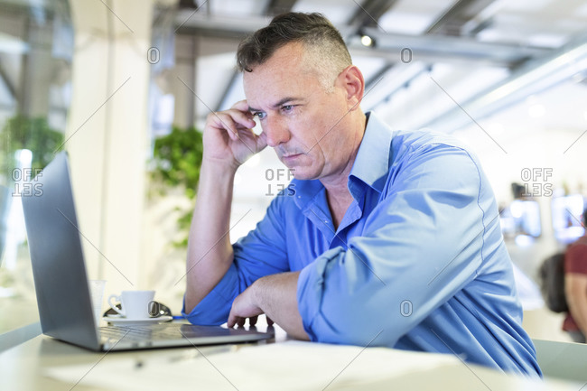 Distressed male professional staring at laptop while sitting in coffee shop