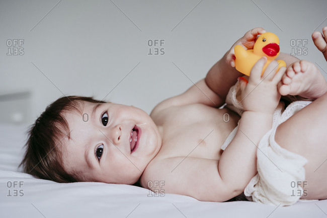 Smiling cute baby boy playing with duck toy while lying down on bed at home