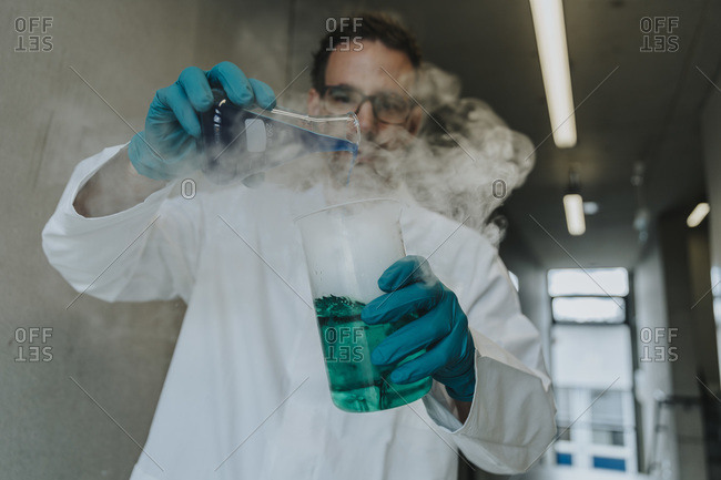 Scientist mixing liquid solution in flask while standing at clinic corridor