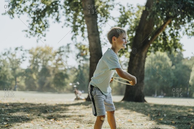 Little boy throwing frisbee ring while standing in public park on sunny day