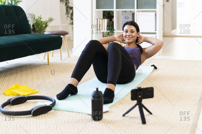 Young woman doing crunches with hands behind head while lying down at home