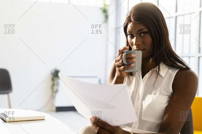 Young woman with coffee cup reading paper while sitting on chair at office
