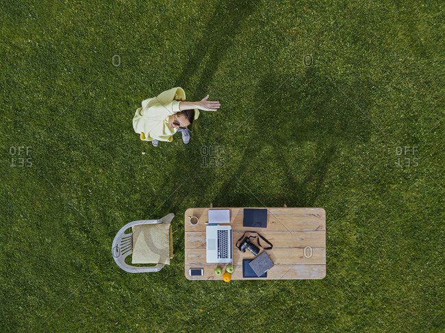 Aerial view of woman stretching in front of coffee table set on green lawn