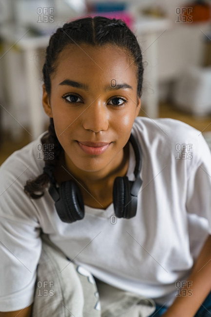 Smiling teenage girl with headphone around neck sitting in bedroom at home