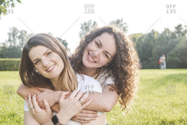 Smiling young woman hugging female friend from behind at park on sunny day