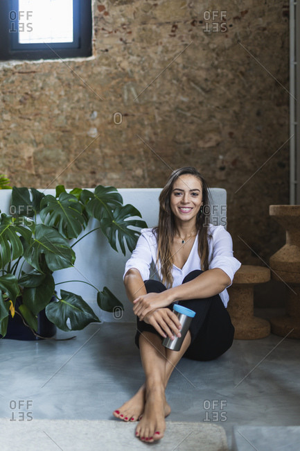 Smiling businesswoman with insulated coffee mug sitting on floor in office