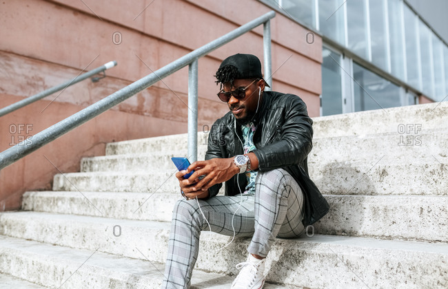 Mid adult man wearing sunglasses using mobile phone while sitting on steps