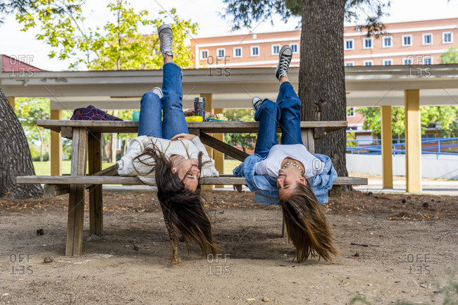 Female friends lying on bench upside down in public park during sunny day