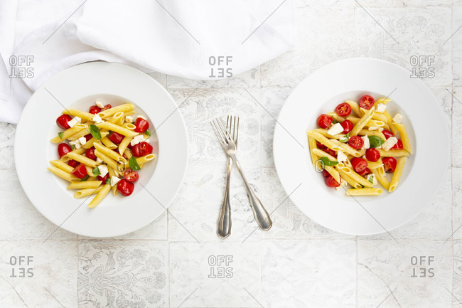 Two plates of vegetarian pasta with mozzarella- cherry tomatoes and basil