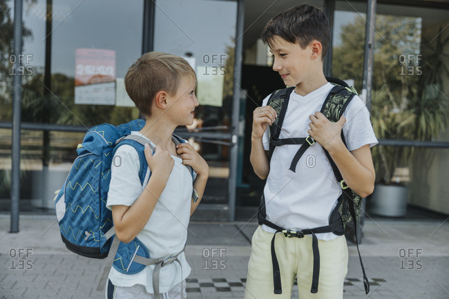 Brothers looking at each other while standing in front of school building