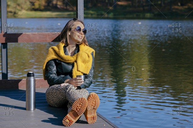 Smiling woman having coffee while relaxing pier over lake during weekend