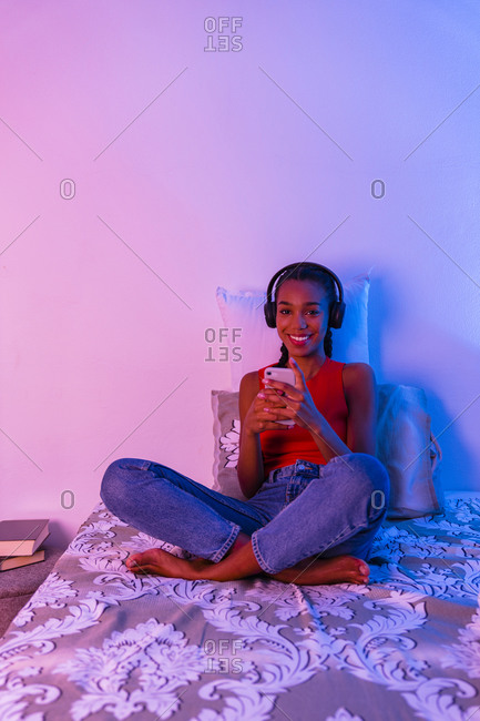 Smiling teenage girl using smart phone sitting on bed at home in bedroom