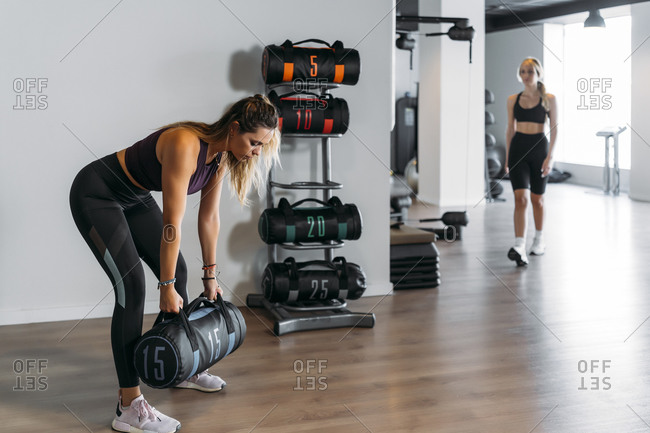 Female athlete lifting punching bag and other sportswoman walking in gym