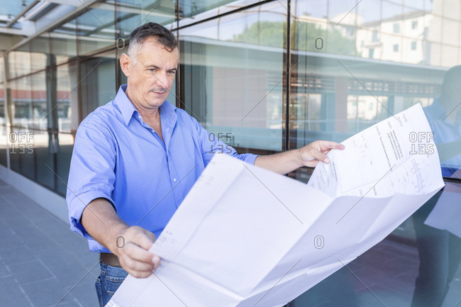 Confident male entrepreneur looking at floor plan while standing in city