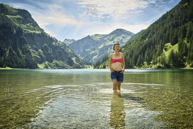 Mature woman knee deep in Vilsalpsee against mountain range on sunny day