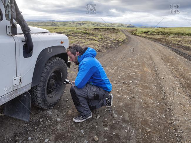 Man kneeling while examining tire pressure through equipment at roadside