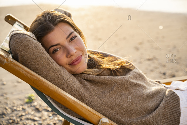 Beautiful young woman reclining on folding chair at beach during sunset