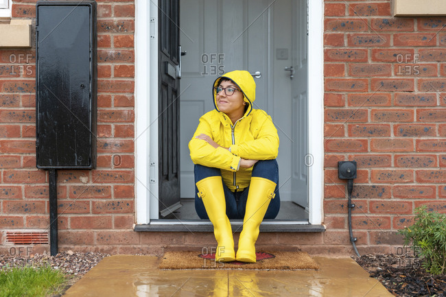 Woman looking away while sitting on doorway at home during rainy season