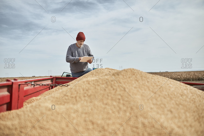 Farmer using digital tablet while standing on tractor against clear sky