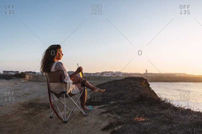 Woman drinking white wine while sitting on chair at beach during sunset