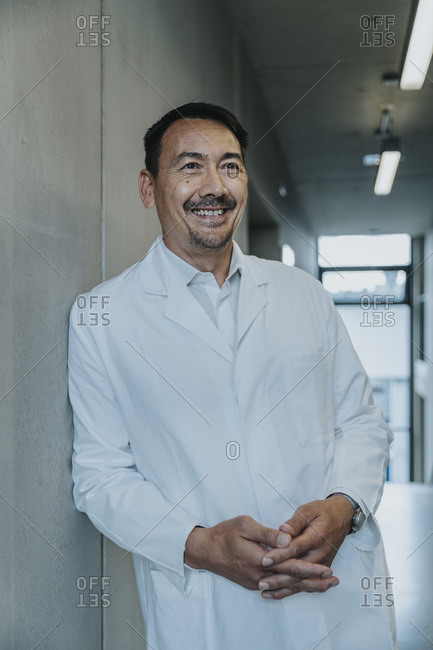 Smiling scientist with hands clasped leaning on wall at clinic corridor