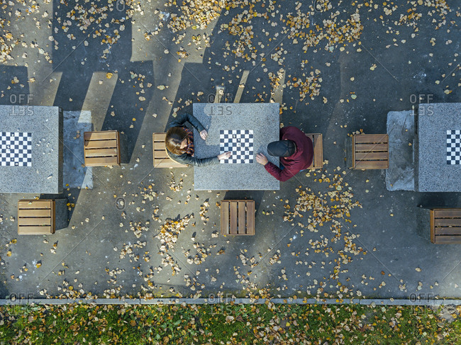 Boyfriend playing chess with girlfriend at table in park during autumn
