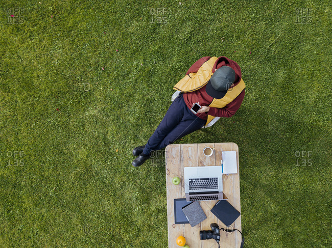 Aerial view of man using smart phone at coffee table set on green lawn