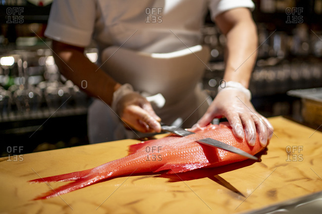 Chef cutting fish on cutting board in commercial kitchen at restaurant