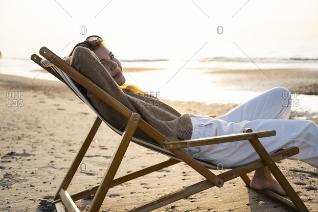 Beautiful young woman relaxing on folding chair at beach during sunset