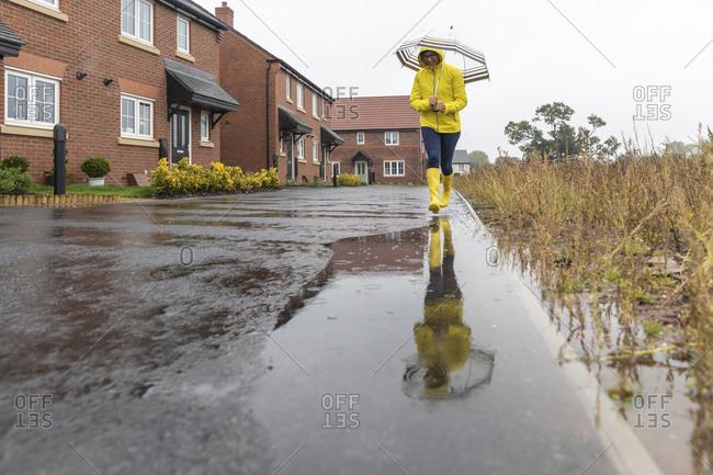 Woman holding umbrella walking in puddle on street during rainy season