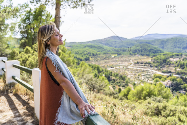 Relaxed blond mature woman standing with eyes closed at health retreat