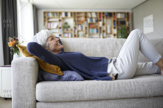 Smiling senior woman with hands behind head lying down on sofa at home