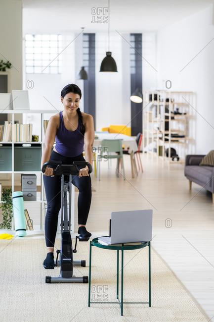 Female athlete exercising on exercise bike while using laptop at home