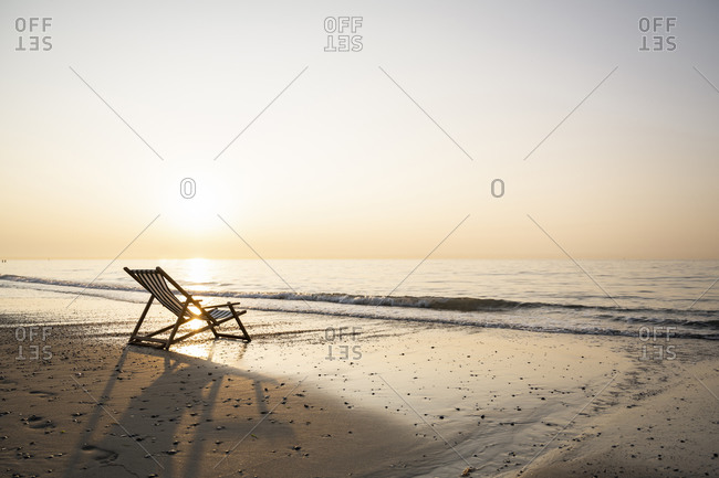 Empty folding chair on shore at beach against clear sky during sunset