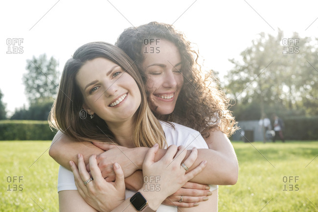 Beautiful woman being hugged from smiling young female friend at park