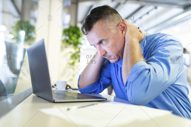 Distressed businessman staring at laptop while sitting in coffee shop