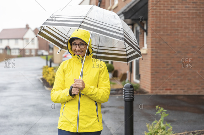 Smiling woman holding umbrella standing on street during rainy season